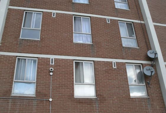 Toronto apartment building with open windows in early December, indicating overheating.